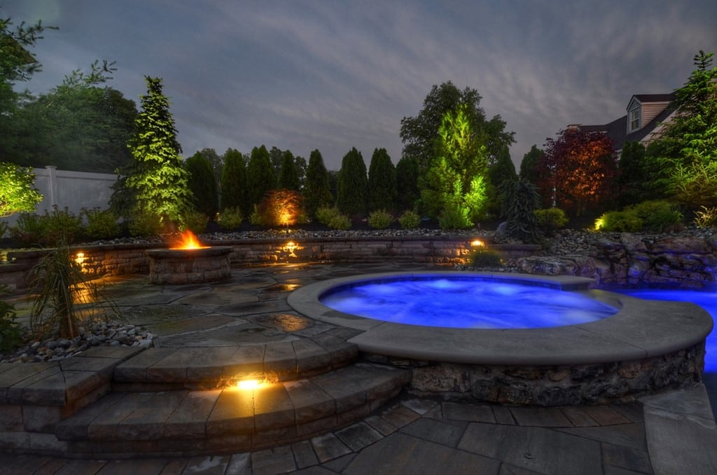 Stone pool terraces with hot tub, firepit and lighting