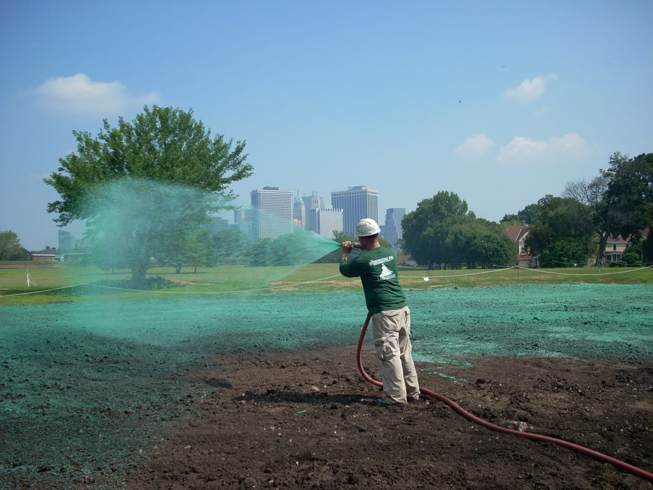 Hydroseeding Pro employee spraying seed mix at Governer's Island