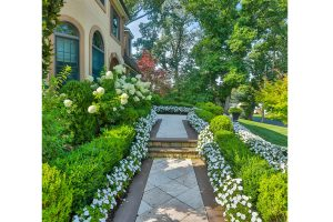 Front of Home with Beautiful Garden Lining the Walkway to the Door