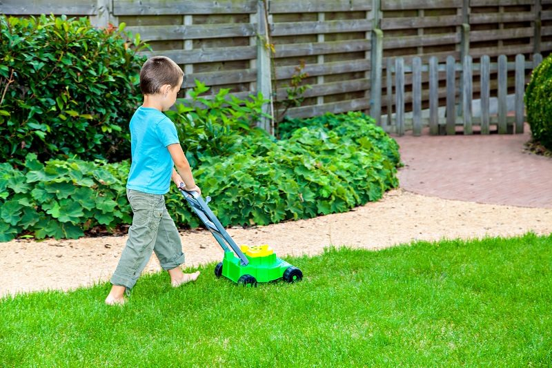 kid mowing grass