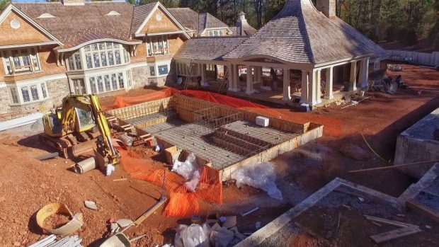 Aerial view of landscape construction in progress of patios, pool, stone wall, and pavilion