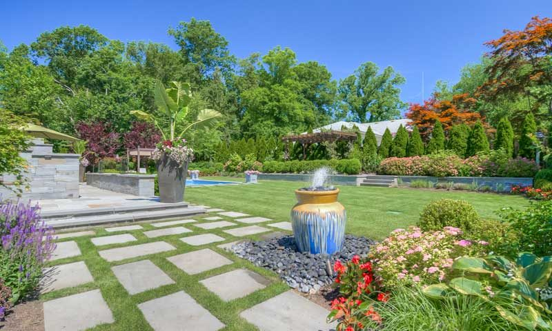 Backyard path with fountain and colorful pink, red, and purple plants, plant-along-high-traffic-areas