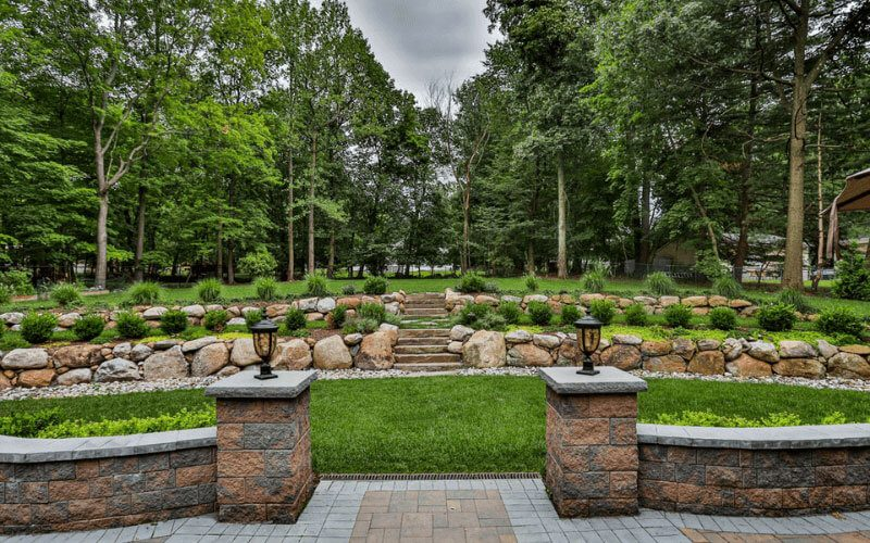 Retaining wall with paver patio and hillside landscaping