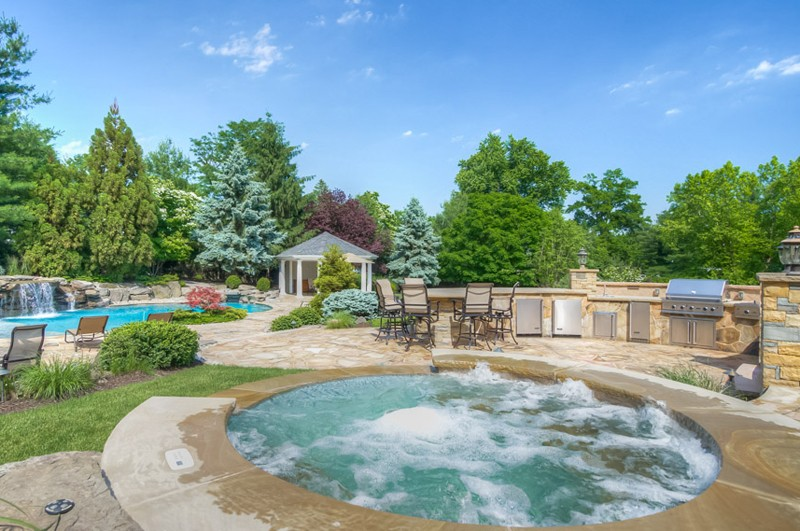 Outdoor Kitchen surrounded by Pool, Jacuzzi, and Pool Deck