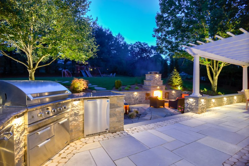 Patio with Outdoor Kitchen. Pergola, and Fireplace, and Custom Landscape Lighting