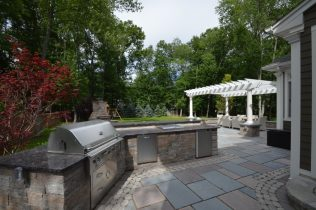 Outdoor Kitchen with BBQ, Regrigerator, and Storage with Stone Veneer