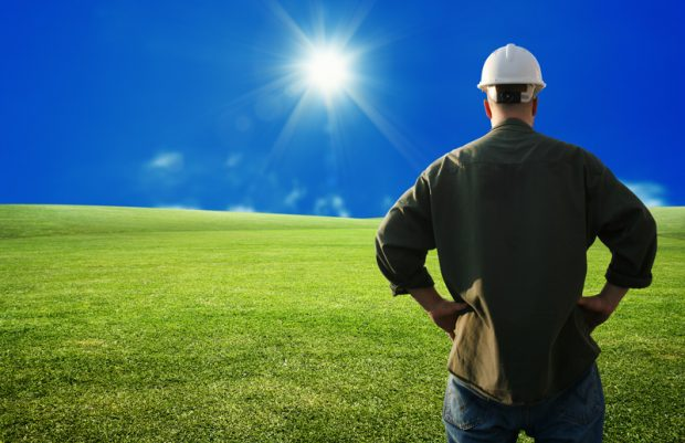 Landscaper looking over a large expanse of grass