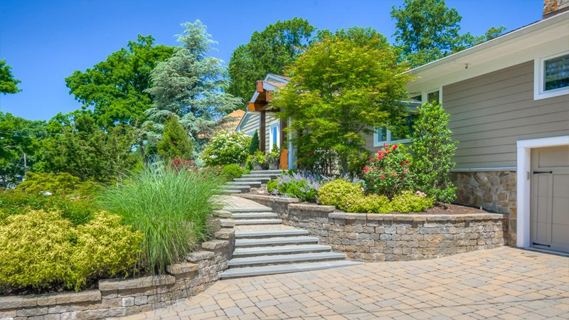 Retaining walls and dramatic stairs leading to entrance of home